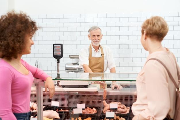 カウンターの後ろで生肉製品を選ぶ女性。
