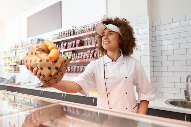 カウンターからソーセージを与える女性の肉屋。