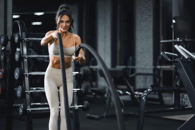 バトルロープトレーニングを行うブルネットの女性。