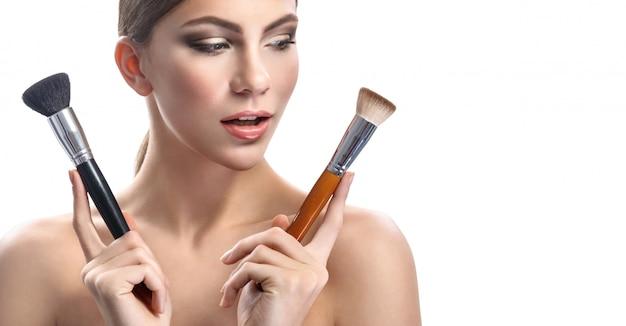 Великолепная молодая женщина, держащая макияж кисти, изолированные на белом