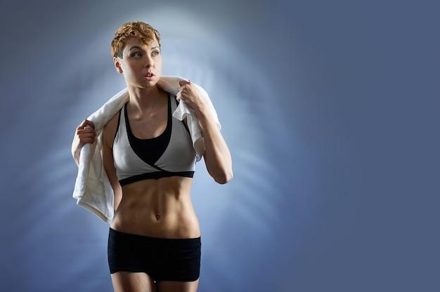 フィット感。ポーズスポーツ服を着ている女性のフィットネストレーナー