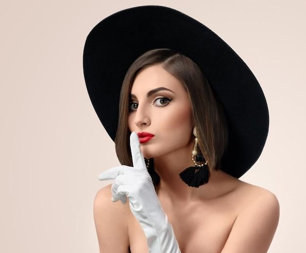 エレガントなファッショナブルな女性がスタジオで帽子をかぶってポーズ
