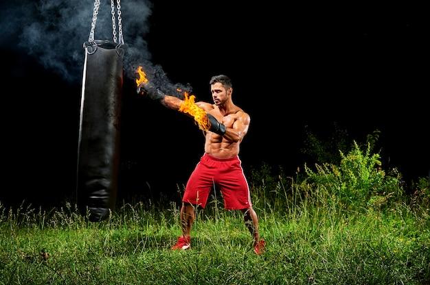 彼のボクシンググロで屋外の土嚢をパンチプロボクサー
