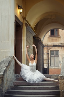 古い建物の近くで踊る美しいバレリーナ