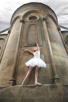 Балерина выступает возле старого замка