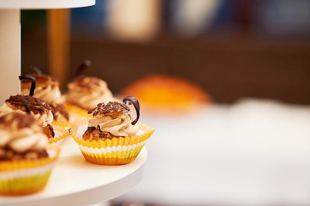 クリームで飾られたおいしいカラメルバニラカップケーキのクロップドクローズアップ