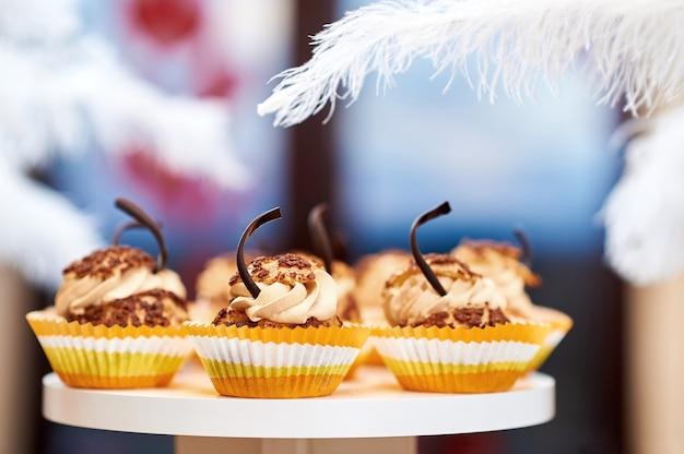 おいしいカラメルバニラカップケーキとココアクリームのサービングの近く