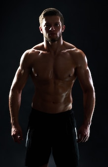 若い筋肉フィットスポーツマンが黒い背景に上半身裸でポーズ