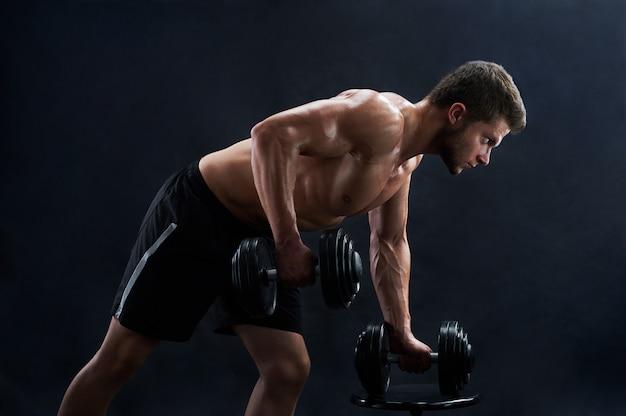 黒の背景にウェイトを持ち上げる筋肉の若い男