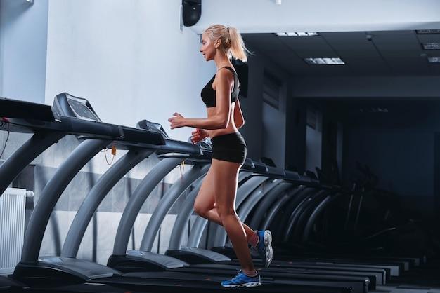 Молодая красивая спортивная женщина работает на беговой дорожке в тренажерном зале