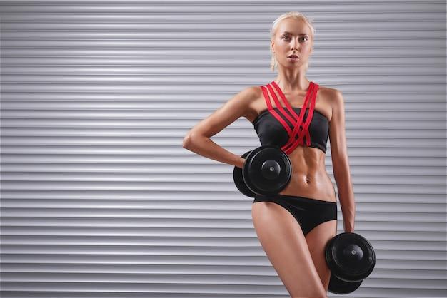 Красивая подходит молодая спортсменка упражняется с гантелями