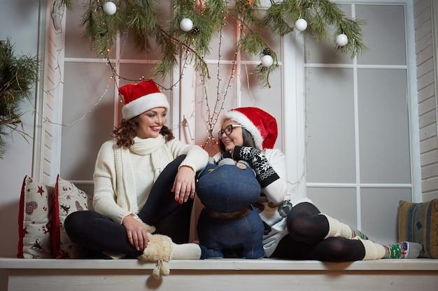 Счастливая мать и дочь, сидя на подоконнике на рождество е
