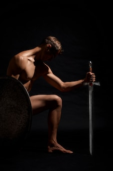 Воин с мечом стоит на коленях.