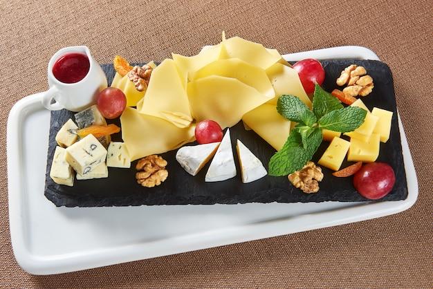 Вид сверху на сырную тарелку с сыром гауда, сыром бри, грецкими орехами, виноградом и баночкой варенья