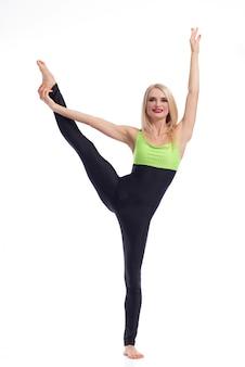 体操選手の女性が彼女の足を片側に伸ばして片足でバランスをとる