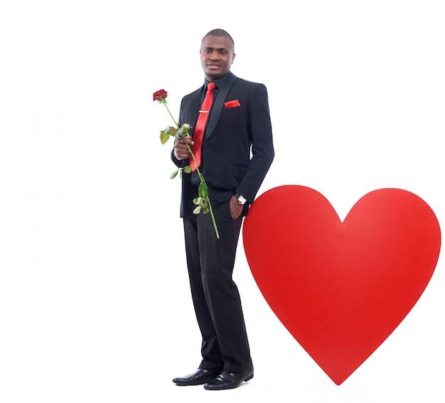 バレンタインの日に赤いバラ、ロマンチックなプレゼントを保持しているハンサムなアフリカ人の肖像画