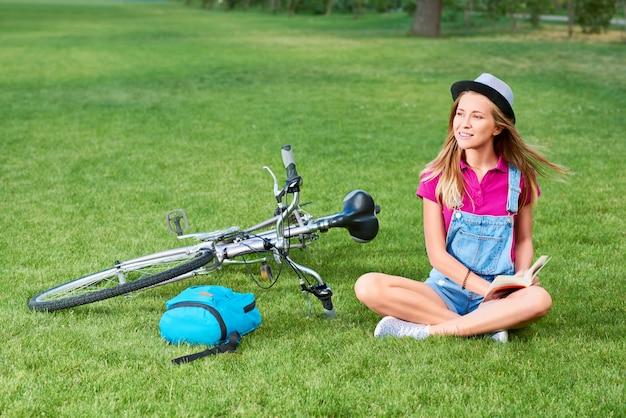 サイクリング本を読んでサイクリング後公園で芝生で休んで美しい若い女性サイクリストのショットレクリエーション趣味文学インテリジェンス幸福ライフスタイル夏のコンセプト。