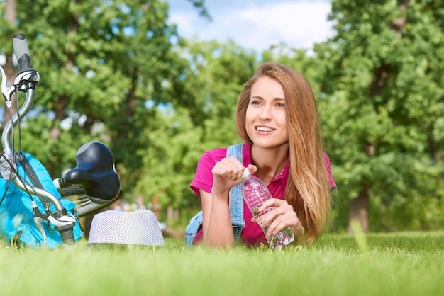 コピースペースアクアハイドレーションヘルシーヘルスヘルスケアアクティブフィットネスライフスタイルポジティブバイタリティをサイクリングした後、地元の公園の芝生の上に横たわっている間水を持っている豪華な若い女性のショット。