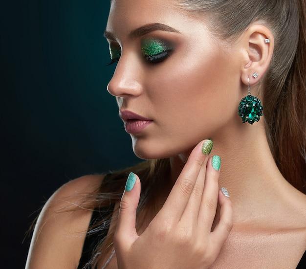 目を閉じて、長いまつげ、緑の色でメイク、ふっくらとした唇、首とあごに触れる魅力的なブルネットの少女の背面図。大きな丸いイヤリング、光沢のあるマニキュアを持つ美しい女性。