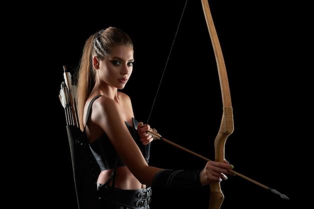 Портрет великолепной молодой длинноволосой женщины-воина с луком, позирующей на черной стене.