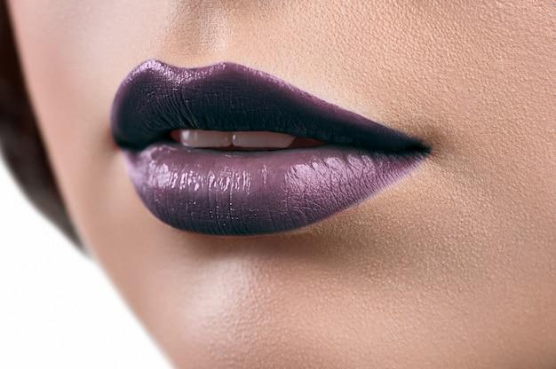 口紅やリップグロスを着て女性の唇のショットを閉じます