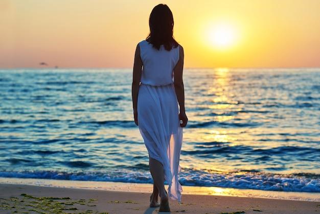 日没の背景に白いドレスで女の子のバックビュー。