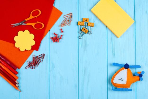 赤とオレンジ色の文房具と青い木製の背景にフェルトヘリコプター。