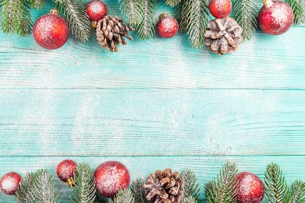 Рождественские баннер с зеленым деревом, красный шар украшения, шишки на мятном деревянном фоне под снегом.
