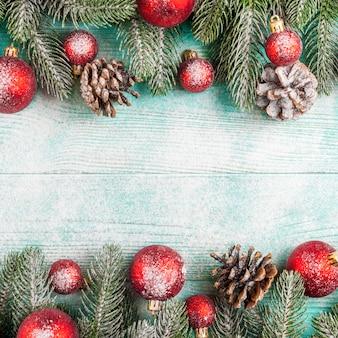 緑の木、赤いボールの装飾、雪の下でミントの木製の背景上の円錐形のクリスマスバナー。