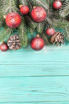 Новогодний баннер с зеленым деревом, шариковые украшения, шишки на деревянном текстурированном фоне