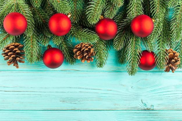 Рождественские баннер с зеленым деревом, красный шар украшения, шишки на мятном деревянном фоне.