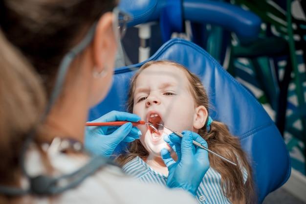 歯の椅子に座っている少女。乳歯のケアの概念