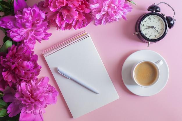 ピンクのパステル調の背景にペンで空のノートブック