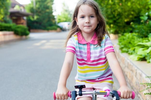 子供たちは家の近くで自転車に乗る。晴れた夏の日に自転車の女の子。幼児のためのアクティブで健康的なアウトドアスポーツ。赤ちゃんのコンセプトのための楽しい活動