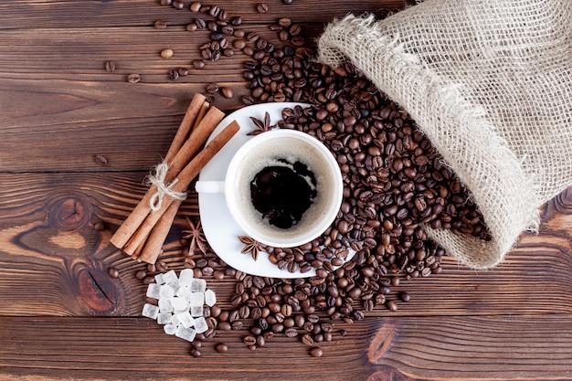 コーヒーカップとテーブルの上のコーヒー豆