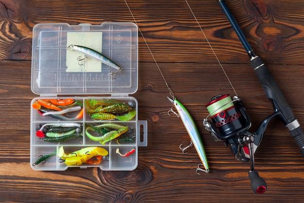 暗い木製のテーブルの上の釣り道具。トップビュー。