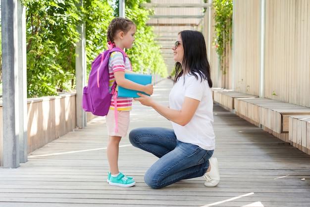Первый день в школе. мама воспитывает маленького ребенка школьницей в первом классе. концепция обратно в школу
