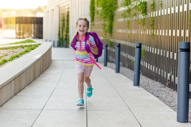 Концепция обратно в школу. первый день школы. счастливый ребенок девочка бежит в класс.