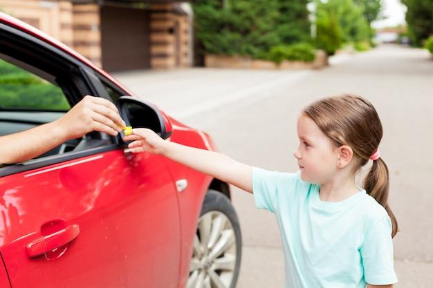 車の中で見知らぬ人が子供にキャンディを提供します。危険にさらされている子供。子供たちがコンセプトを誘します。