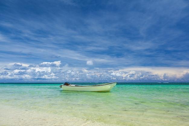 カリブ海の海岸に立っている空の白いボート。美しい白い砂浜、ターコイズブルーの海、青い空。
