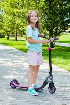 日当たりの良い夏の日に都市公園でスクーターに乗ることを学ぶ小さな子供。子供向けのアクティブで健康的なレジャーとアウトドアスポーツ。