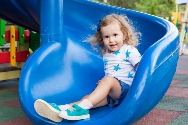 日当たりの良い夏の日に屋外の遊び場で楽しんでいるかわいい女の子。プラスチック製のスライドの子。子供のための楽しい活動。