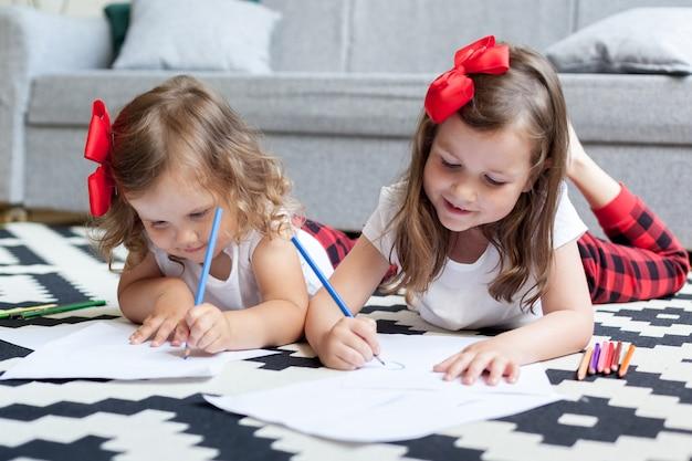 Две сестренки маленьких девочек лежат на полу дома и рисуют цветными карандашами на бумаге.