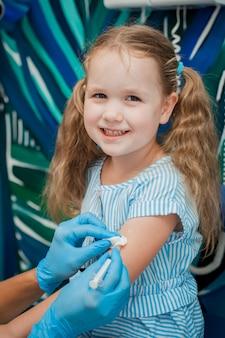 医者は小さな女の子の手に注射をする