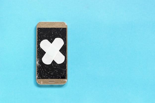 割れた画面を持つ壊れた携帯電話はバンドエイド医療石膏を覆わ