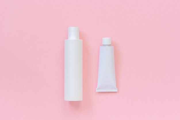 空白の化粧品または医療用の白いプラスチックボトルとクリーム、シャンプー、軟膏、歯磨き粉のブリキチューブ