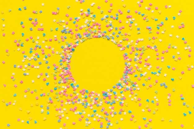 黄色い紙の上の散乱多色菓子トッピングドレッシング。
