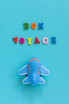 Счастливого пути и детский забавный игрушечный самолет на синем фоне. концепт путешествия, туризм