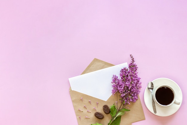 テキストと一杯のコーヒーのための白い空の空白カードでクラフト封筒にライラックの枝