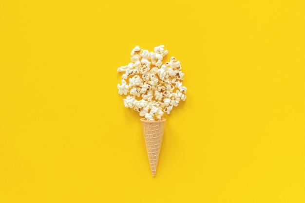 黄色の背景にアイスクリームワッフルコーンに散在ポップコーン